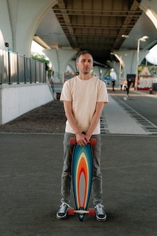 Millennial man hold skateboard or longboard indoors in urban space for extreme skating trainings