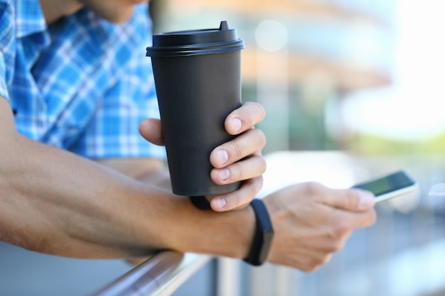 Millennial man hold smartphone with coffee cup