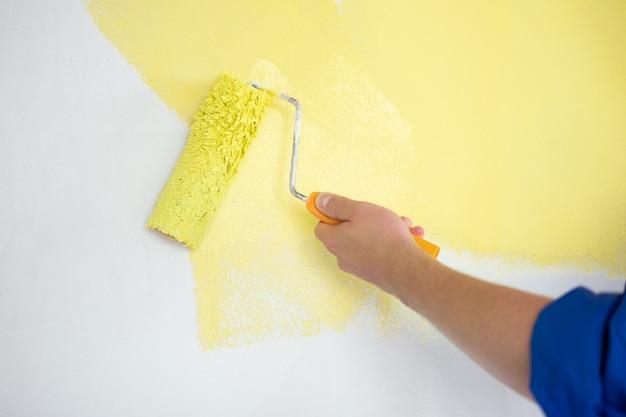롤러 리노베이션 수리 및 재장식 개념으로 노란색으로 벽을 칠하는 밀레니엄 남자