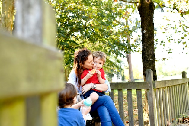 Millennial mother kissing her three year old son after school in a park while he eats a snack