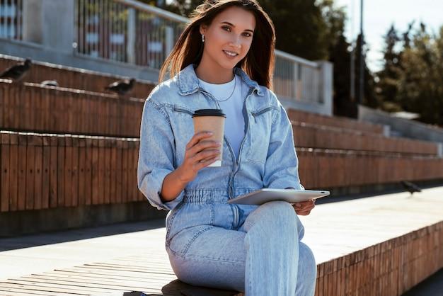 デニムの服を着たミレニアル世代の女性が公園のベンチに座って、スマートタブレットを手に持っています。女性はタブレットを使用しています