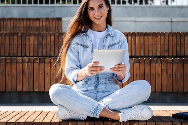 デニムのミレニアル世代の女性は、スマートタブレットを保持している公園のベンチに座っています。