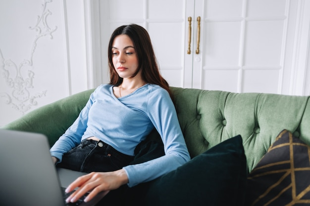 Миллениал женщина сидит дома и работает на ноутбуке