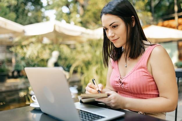 Тысячелетняя молодая латиноамериканка работает или учится на ноутбуке, сидя в кафе - бизнесвумен-фрилансер, делая заметки в блокноте во время просмотра видеозвонка - концепция внештатных людей