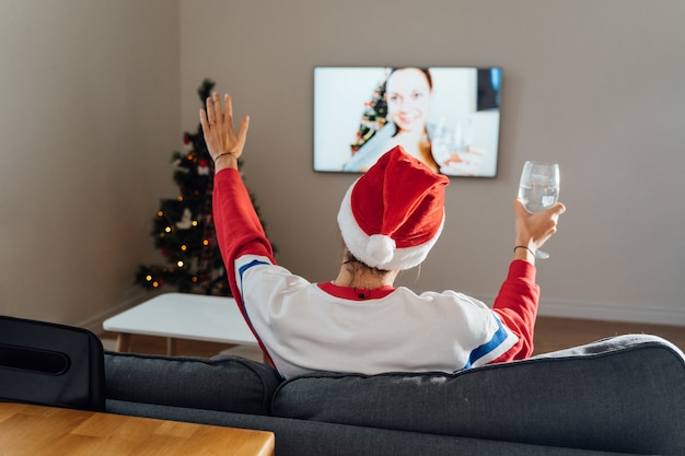 Millennial young woman using phone at home in christmas eve. online holiday shopping, quarantine