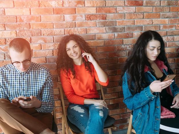 ミレニアル世代のビジネスライフ。スマートフォンを使用して、ロフトワークスペースで働く若者。