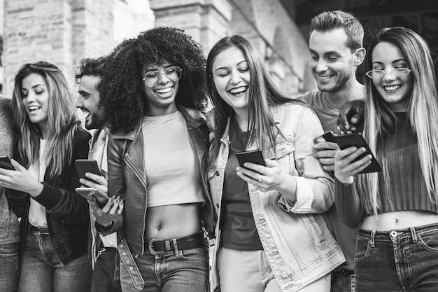 Millennials friends walking together outside of university - young students having fun using smartphones - youth, lifestyle, friendship and mutiracial concept - focus on two center girls faces