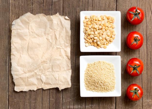 ボウルにミレットとスプリットイエローピース、ペーパーコピースペースを持つ木製テーブルトップビューでトマト