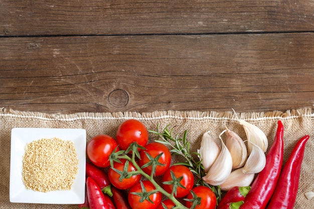 Millet in a bowl, raw vegetables and herbs on a wooden table top view with copy space