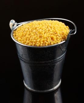 Millet in a bucket on a dark surface