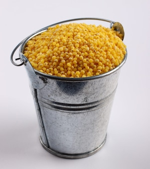Millet in a bucket on a white surface