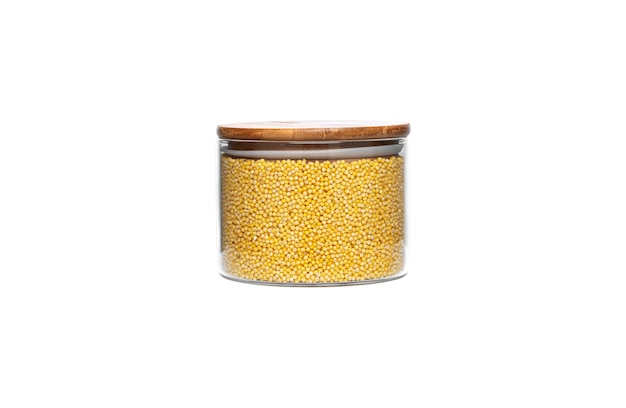 Millet cereal in a glass jar isolated.