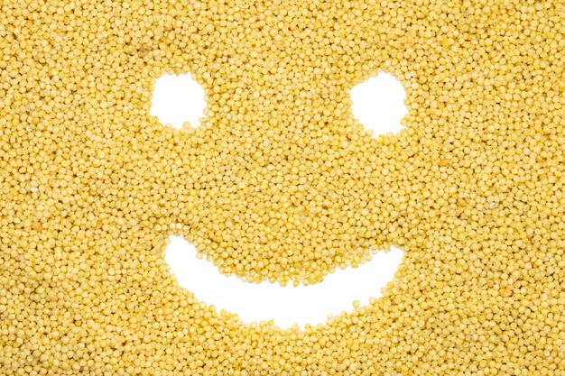 Millet groats, funny smile face, close up, top view.