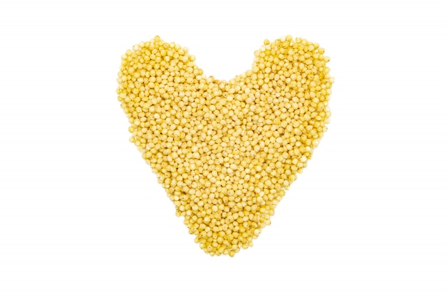 Millet groats, heart-shaped, close up, isolated, top view.