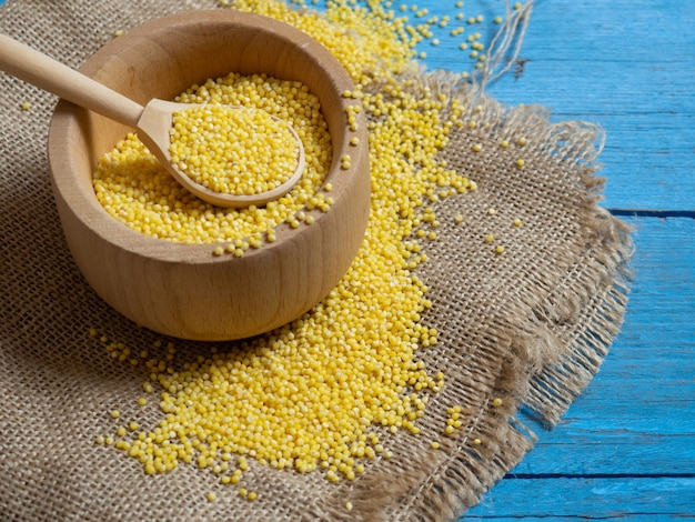 Millet. millet in a wooden spoon and bowl on a wooden kitchen table