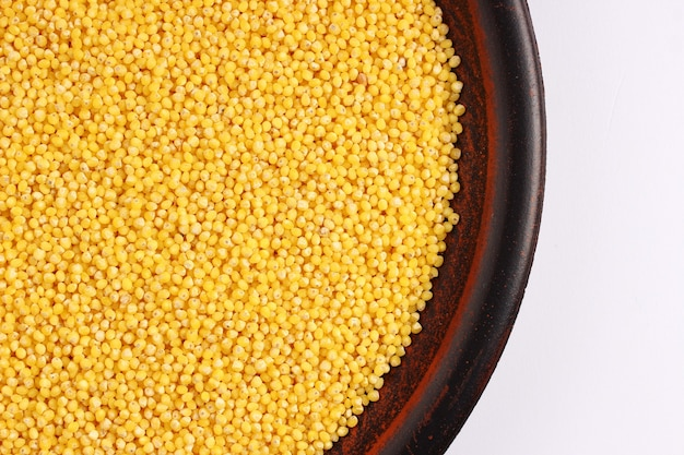 Millet in a plate on a white surface place for text cope space