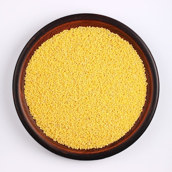 Millet in a plate on a white surface