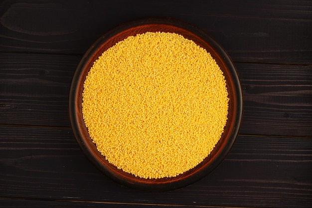 Millet in a plate on a wooden surface