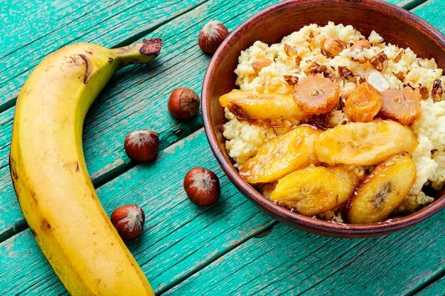 캐러멜 처리된 바나나와 견과류를 곁들인 기장 죽.건강한 아침 식사