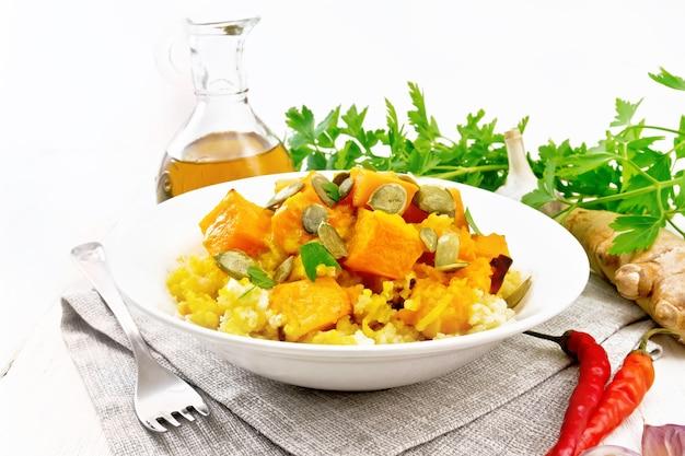Пшенная каша с острым тыквенным соусом и семенами в тарелке на салфетке на фоне деревянной доски