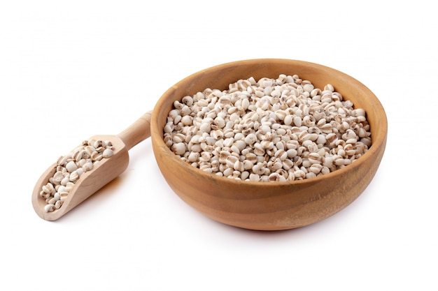 Millet rice in a wooden bowl isolated on white background