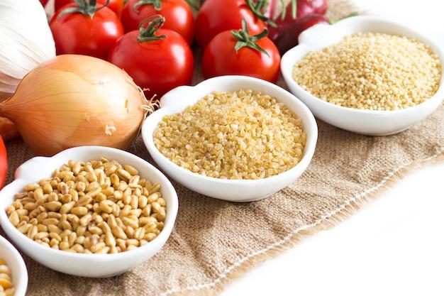 ボウルにミレット、スペルト、イエローピース、白で隔離生野菜をクローズアップ
