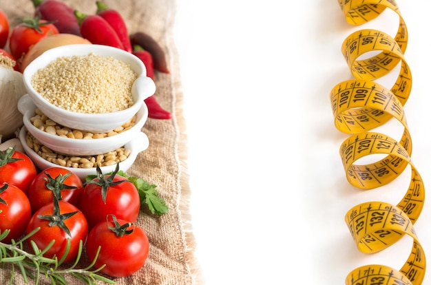 Millet, spelt, yellow peas and raw vegetables with measuring tape isolated on white close up