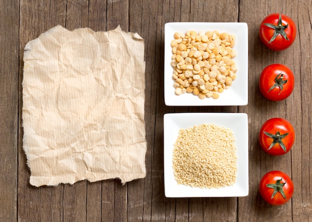 Millet and split yellow peas in bowls, tomatoes on a wooden table top view with paper copy space