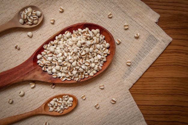 Millet in a wooden spoon that is cereal and food on a brown tablecloth, wood grain
