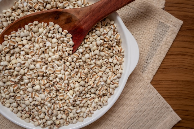 Millet in a wooden spoon that is cereal and food on a brown tablecloth