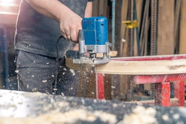 가구 만드는 일에 손으로 전기 커터로 둥근 나무 창 밀링