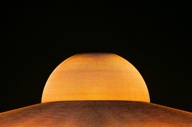 Million golden buddha figurine of dhammakaya pagoda at wat dhammakaya at night.