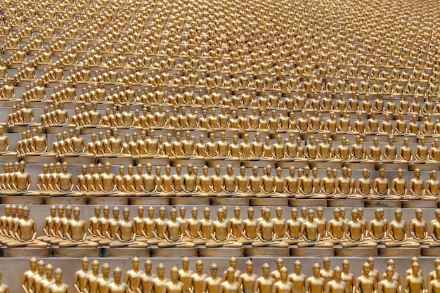 Million golden buddha figurine in wat phra dhammakaya. buddhist temple in north of bangkok, thailand. this is one of the largest temples in thailand. religion concept. close up