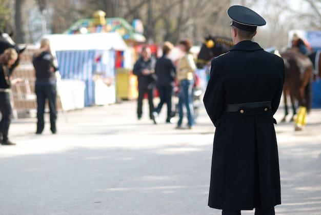 Военный человек смотрит на идущих людей