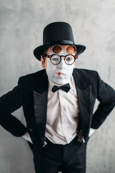 Mime actor in glasses and makeup mask. pantomime in suit, gloves and hat.