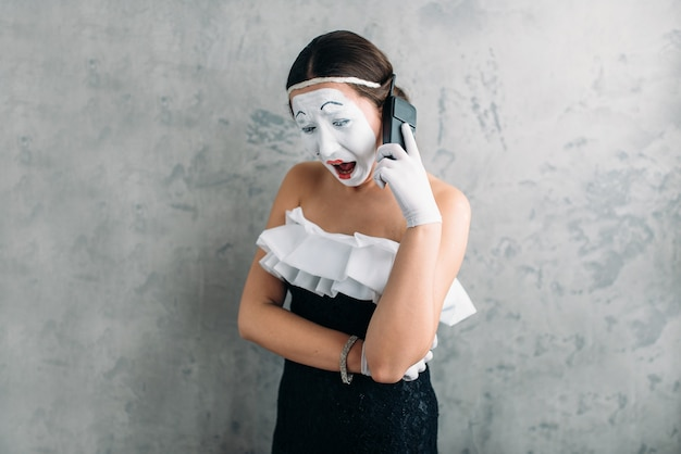 Mime actress performing with mobile phone. comedy female artist posing