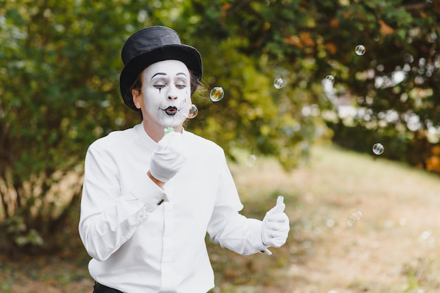 Mime artist blowing a bubble