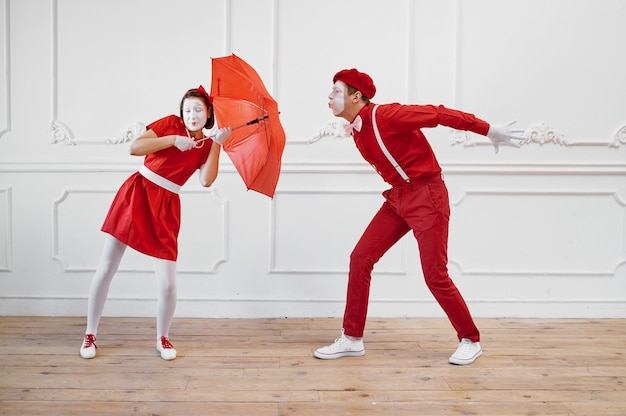 Mime artists, scene with umbrella in windy weather