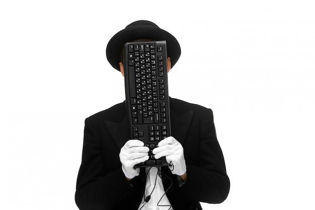 Мим как бизнесмен держит клавиатуру на лице