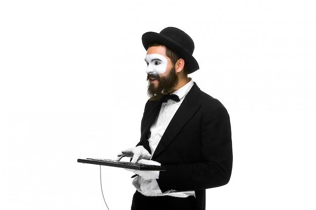 Mime as a businessman holdinga keyboard