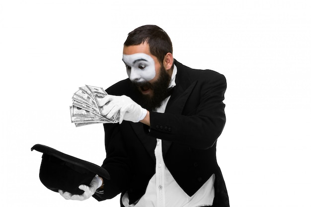 Mime as a businessman laying dollars in hat