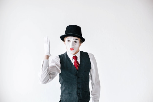 Mime in black hat holds his hand up like a pupil
