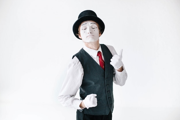 Mime in black hat and waistcoat dances on white background