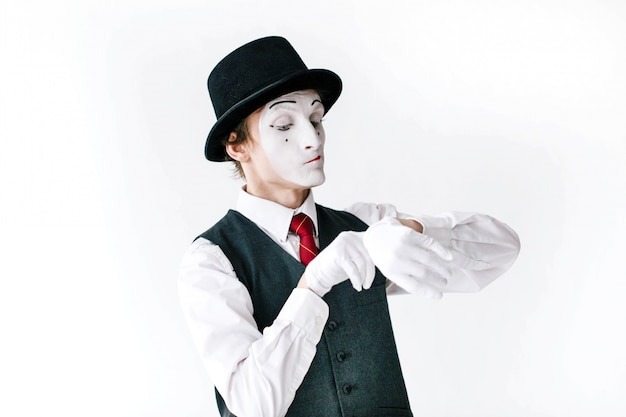 Mime in black hat and waistcoat looks at the invisible watch