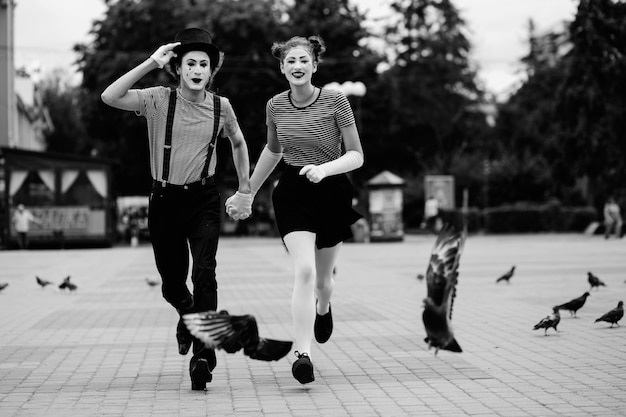 Mime couple holding hands running on pavement