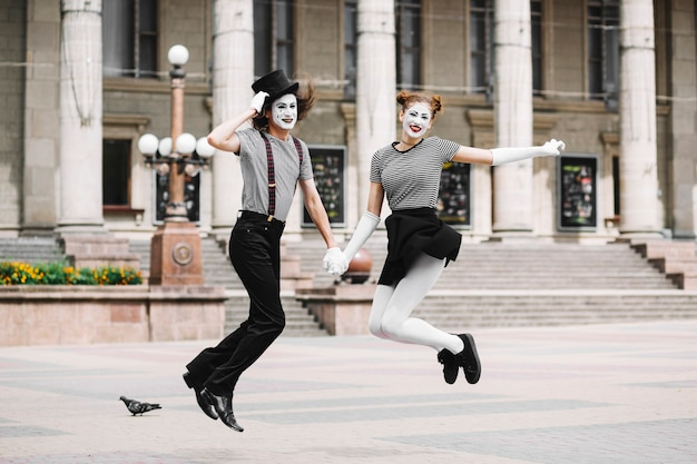 Mime couple jumping in front of building