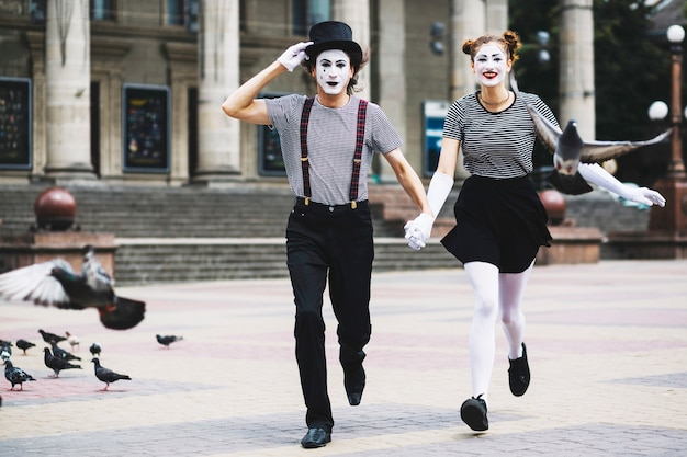 Mime couple running on city pavement
