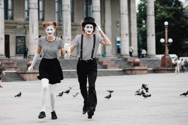Mime couple running in front of building
