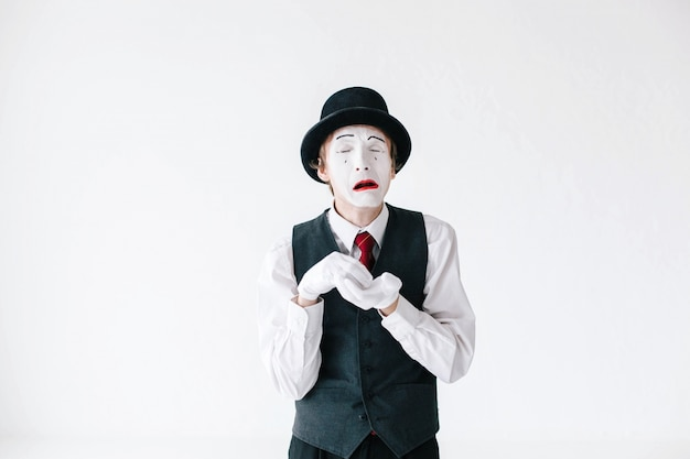 Mime cries holding his hands in white gloves together