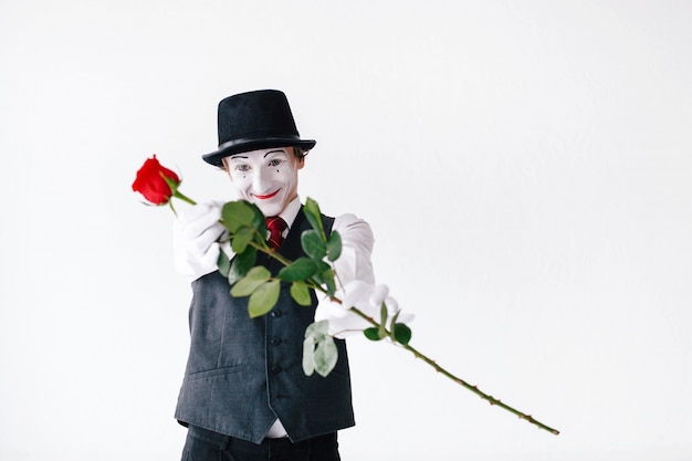 Mime in hat and waistcoat reaches out his hands with red rose